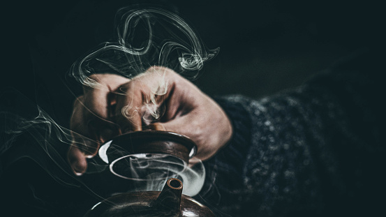 close-up male hand closed the lid of a clay teapot made of yixing clay. beautiful steam from a clay teapot. Yixing clay teapot. High Quality Photo