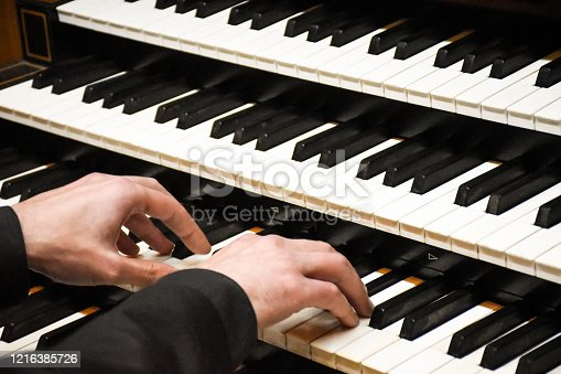 Close-up male musician hands playing the pipe organ