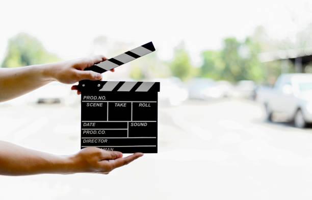 closeup mannhände halten film klöppel mit soft-fokus und mehr licht im hintergrund - oscar filme stock-fotos und bilder