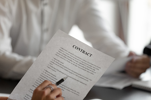 1072035844 istock photo Closeup man holding pen reading terms and conditions of contract 1233104448