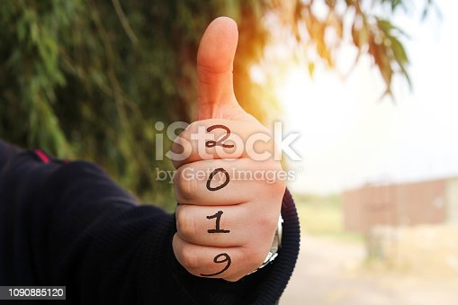1054929988 istock photo closeup man showing thumbs up with 2019 numbers, new year concept 1090885120