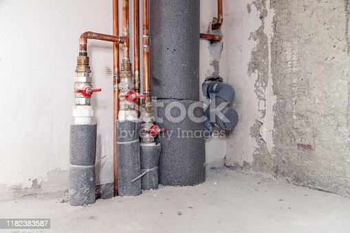 istock Closeup many copper and sewer gray plastic pipes, red valves, fittings on concrete wall. Concept installation, replacement, plumbing, repair pipeline, professional master plumber, leakage pipe 1182383587