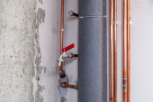 istock Closeup many copper and sewer gray plastic pipes, red valves, fittings on concrete wall. Concept installation, replacement, plumbing, repair pipeline, professional master plumber, leakage pipe 1182383597