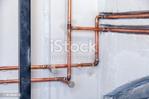 istock Closeup many new sewer copper and plastic pipes, fittings on concrete wall. Concept installation, replacement of plumbing, repair of pipeline, professional master plumber, leakage pipe 1182383615