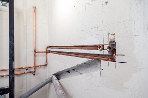 istock Closeup many new sewer copper and plastic pipes, fittings on concrete wall. Concept installation, replacement of plumbing, repair of pipeline, professional master plumber, leakage pipe 1182383628