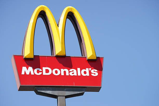 close-up знак mcdonalds на фоне голубого неба. - mcdonalds стоковые фото и изображения