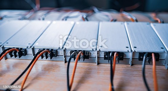 Close-up metal AC-DC power supply with wires lie on wooden table in anticipation of further installation in the production of computer equipment for specialized enterprises. Concept of high-tech powerful equipment