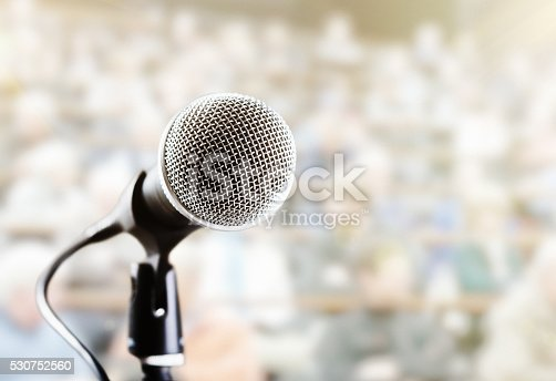 A vocal microphone in front of a defocused audience  on tiered seating who provide ample copy space.