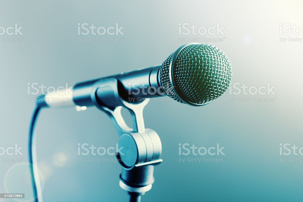 Close-up microphone on stand in smoky, spotlit surroundings stock photo