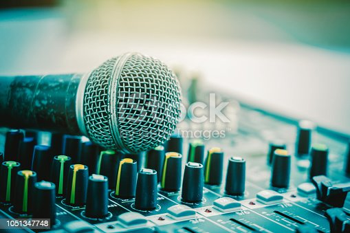 istock Closeup microphone over the audio mixer, vintage film style, music equipment concept 1051347748