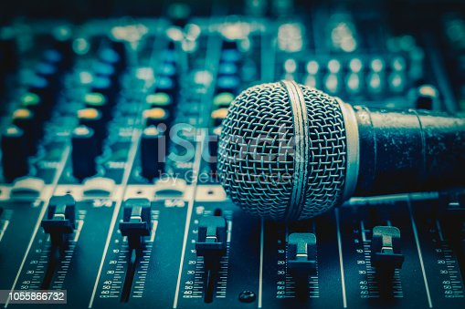 istock Closeup microphone over the audio mixer, vintage film style, music equipment concept 1055866732