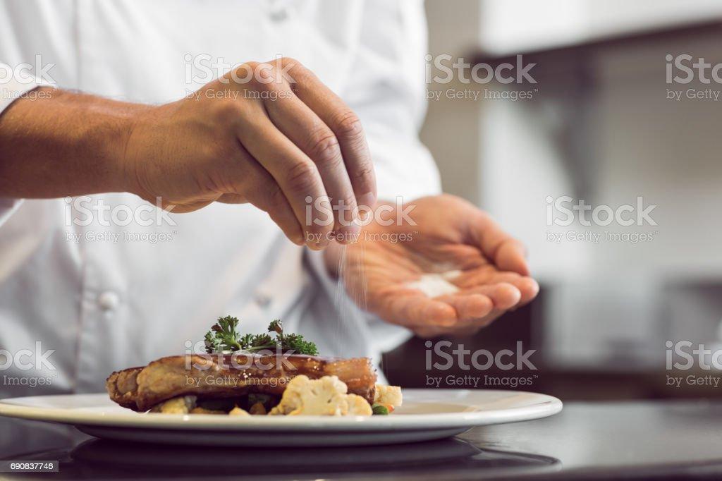 Closeup, section d'un chef mettant sel - Photo