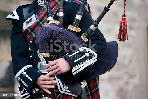 Close up of the hands of a Scottish bagpiper clad in a traditional scottish tartan playing the Scottish bagpipe. Royal Stewart tartan. Outdoor shot in the castle of Edinburgh, Scotland. XXXL (Canon Eos 1Ds Mark III)