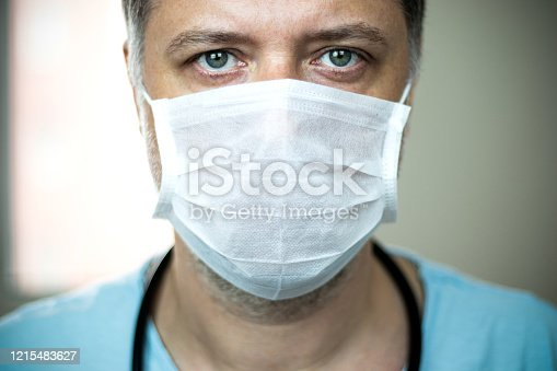 Close-up middle-aged green-eyed doctor with mask on his face