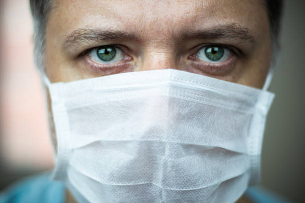 Close-up middle-aged green-eyed doctor with mask on his face stock photo
