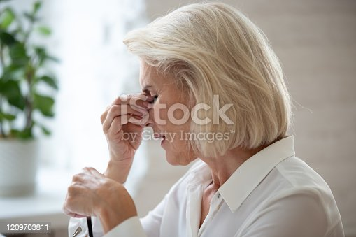 1049512672 istock photo Closeup middle-aged woman taking off glasses reduces eye strain 1209703811
