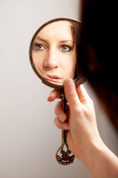 closeup mirror reflection of a woman's face - handspiegel stockfoto's en -beelden