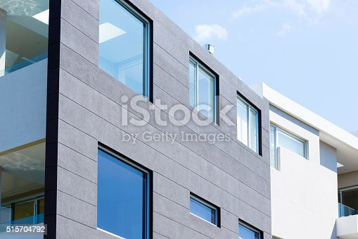 Closeup modern white apartment building with glass balcony against blue sky, full frame horizontal composition with copy space