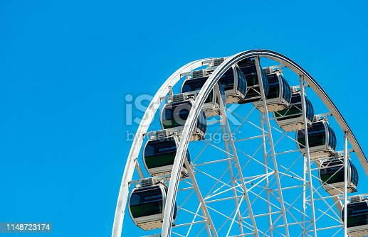 Closeup modern Ferris wheel against blue sky and white clouds. Ferris wheel at funfair for entertainment and recreation on holiday. Modern construction of Ferris wheel in amusement. Fun festival.