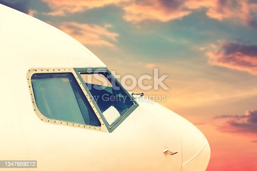 istock Close-up modern passenger commercial airplane cockpit flying against colorful dramatic sunset sky. Detail side view of windows of windshield jet cabin with purple orange blue clouds on background 1347659212