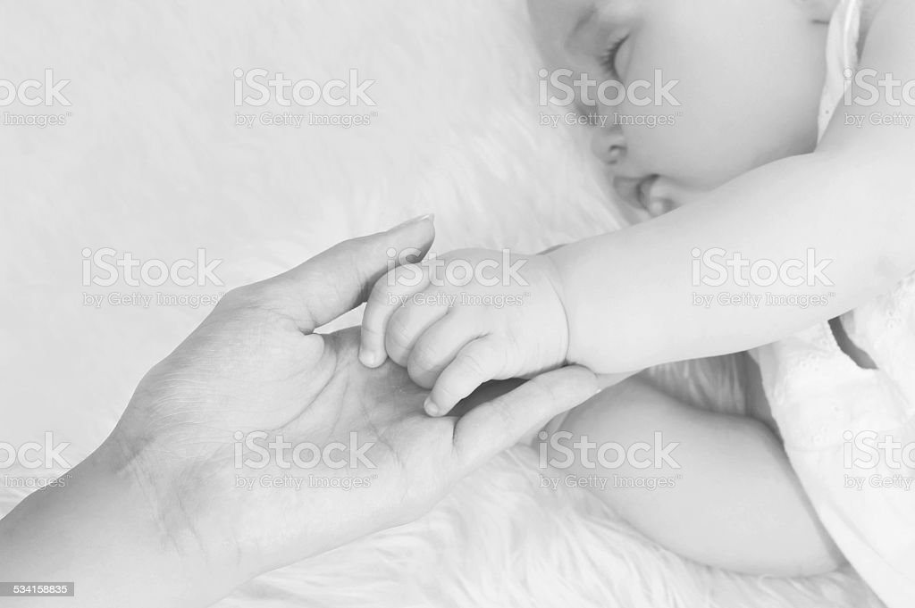 Closeup mother holding hand baby in bed at home stock photo