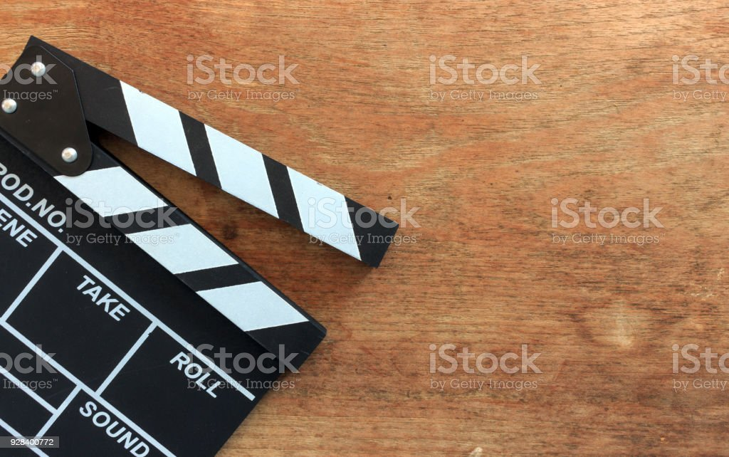 closeup movie clapper board on wood table with soft-focus and over light in the background - foto stock
