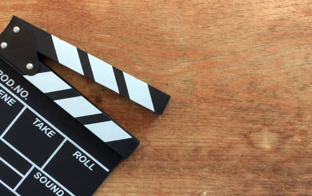 closeup film klappe auf holztisch mit soft-fokus und mehr licht im hintergrund - oscar filme stock-fotos und bilder