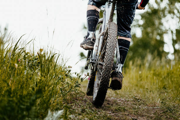 closeup mud mountain bike wheel and legs of cyclist closeup mud mountain bike wheel and legs of cyclist mountain biking stock pictures, royalty-free photos & images
