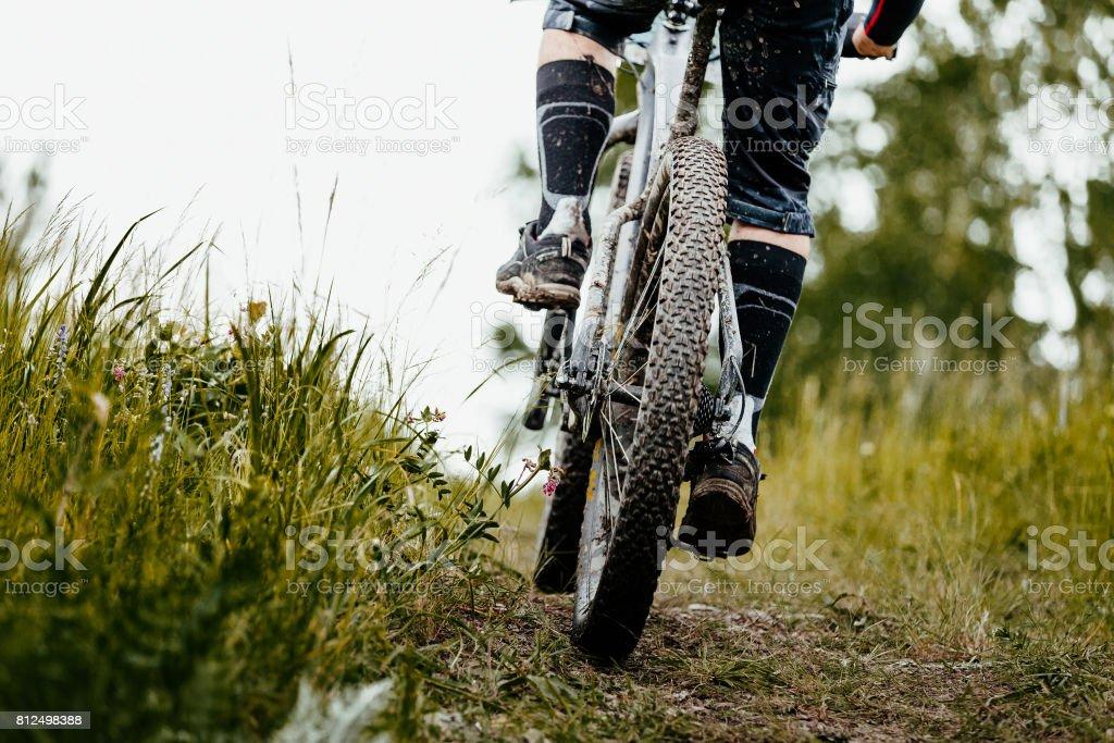 closeup mud mountain bike wheel and legs of cyclist stock photo