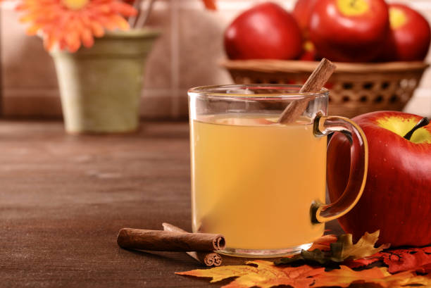 closeup mug of apple cider with cinnamon stick closeup mug of apple cider with cinnamon stick with fall leaves hot apple cider stock pictures, royalty-free photos & images