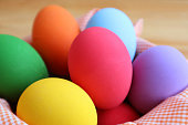 Closeup Multi-colored Easter Eggs in a Basket on Wooden Background