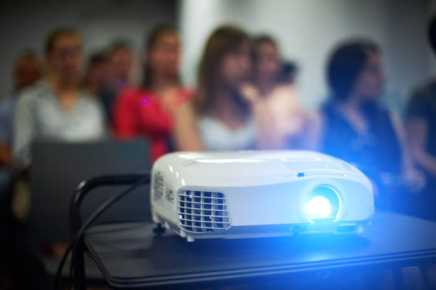 Close-up multimedia projector with blurred people background. stock photo