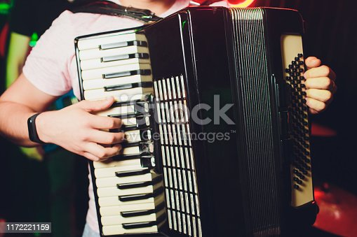 Close-up musician playing the accordion against a black background