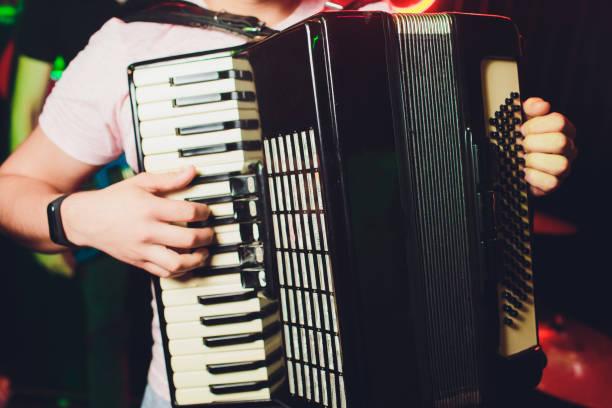 Nahaufnahme Musiker spielen das Akkordeon vor einem schwarzen Hintergrund. – Foto