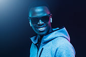 istock Close-up neon picture of African American man wearing wireless earphones and casual gray hoodie 1153003849