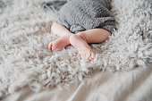 Closeup  newborn baby feet on fluffy blanket. Copy space
