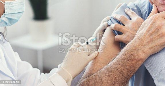 917598714 istock photo Closeup nurse doing vaccination to senior man 1198605916