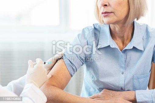 917598714 istock photo Closeup nurse doing vaccination to senior woman 1198240692