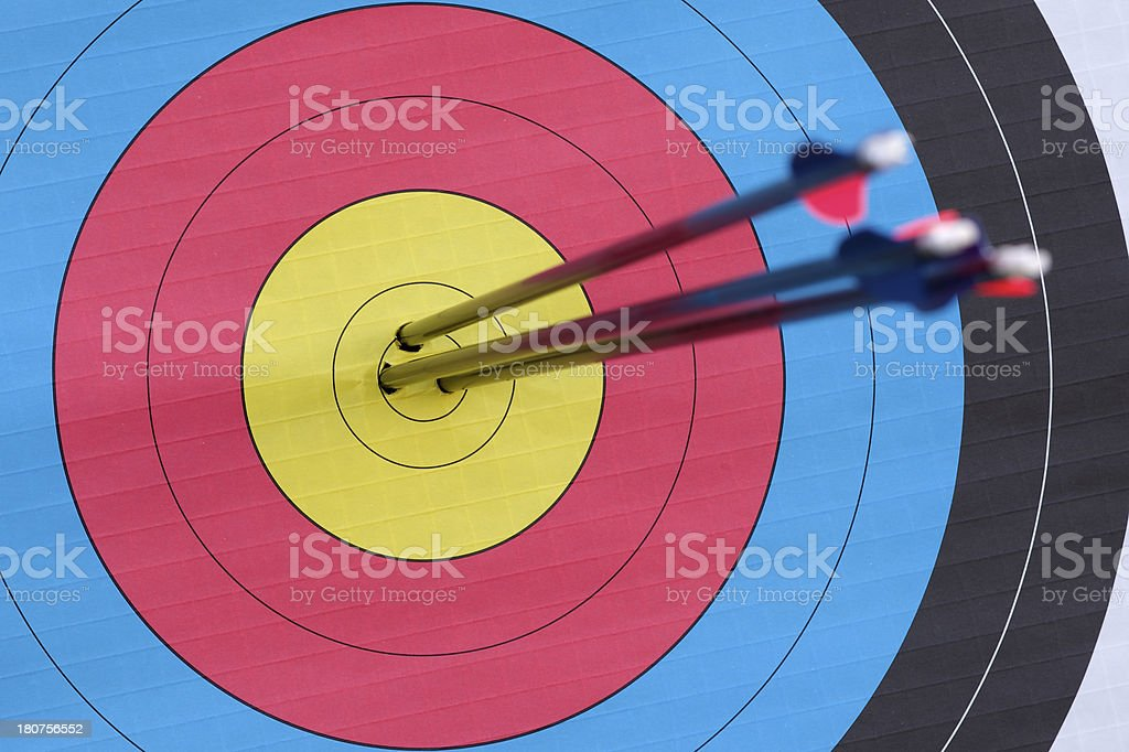 Close-up of 3 arrows in the bullseye of an archery target stock photo