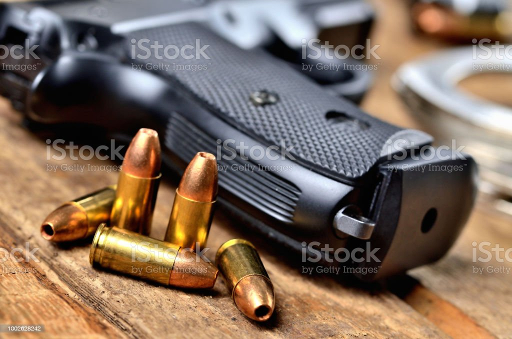 Close-up of 9mm pistol, bullets and handcuffs stock photo