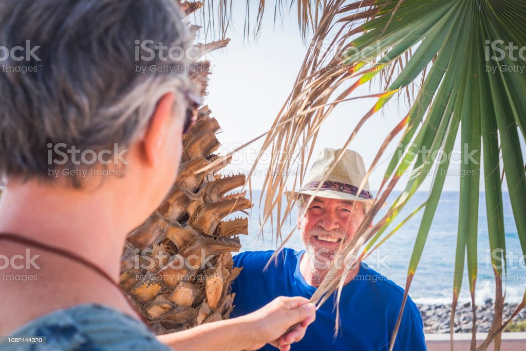 close-up of a 70-year-old man laughing under a palm tree playing hide-and-seek. Vacation, fun concept for senior retired caucasian people - blue sea in background and nice leisure activity stock photo