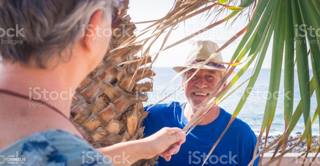 close-up of a 70-year-old man laughing under a palm tree playing hide-and-seek. Vacation, fun concept - Cheerful caucasian aged people in outdoor leisure activity together stock photo