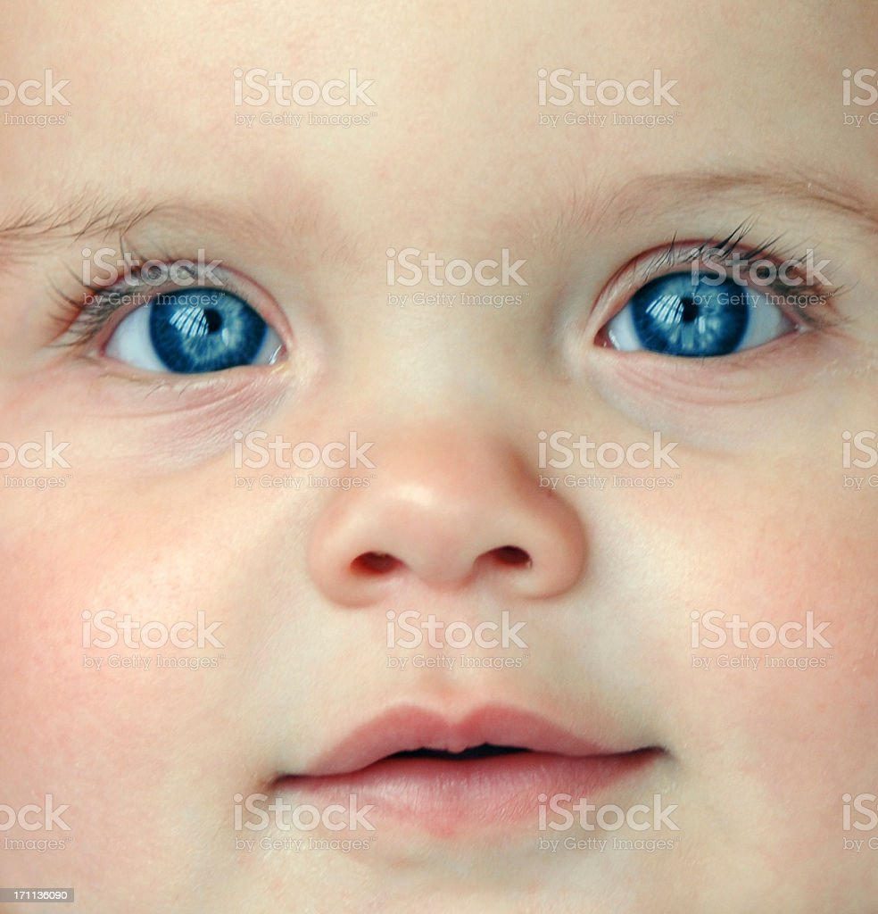 Close-up of a baby's face and blue eyes stock photo