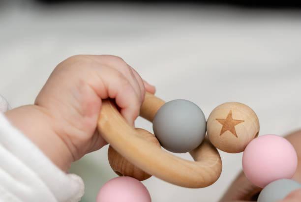 närbild av en barnets hand, leker med en trä leksak. ofokuserat bakgrund - hand tänder ett ljus bildbanksfoton och bilder