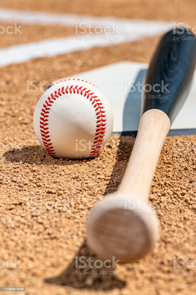 A low angle close-up of a new baseball and a wooden bat painted black...