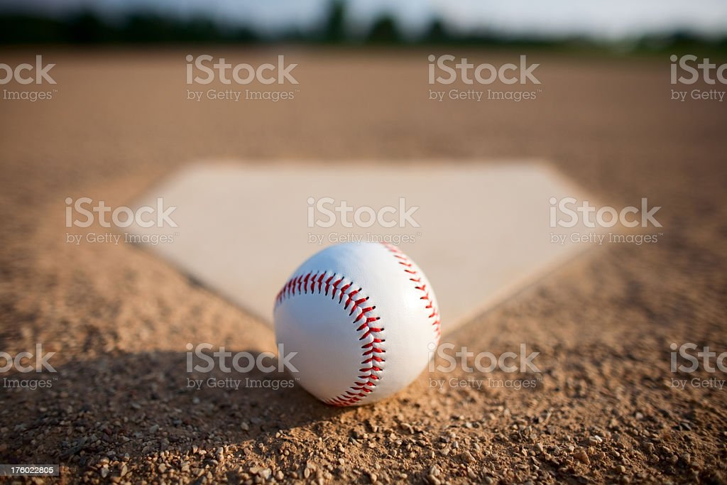 A close-up of a baseball on dirt beside a base plate royalty-free stock photo