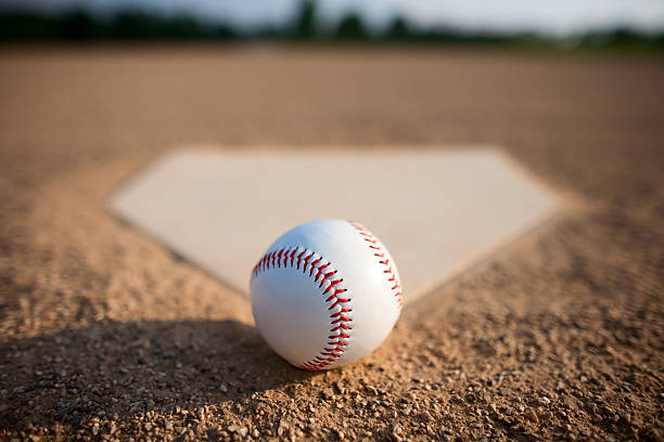 A close-up of a baseball on dirt beside a base plate stock photo