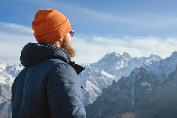 Close-up of a bearded guy in sunglasses with a hat and a down jacket looking at the snow-capped mountains. stock photo