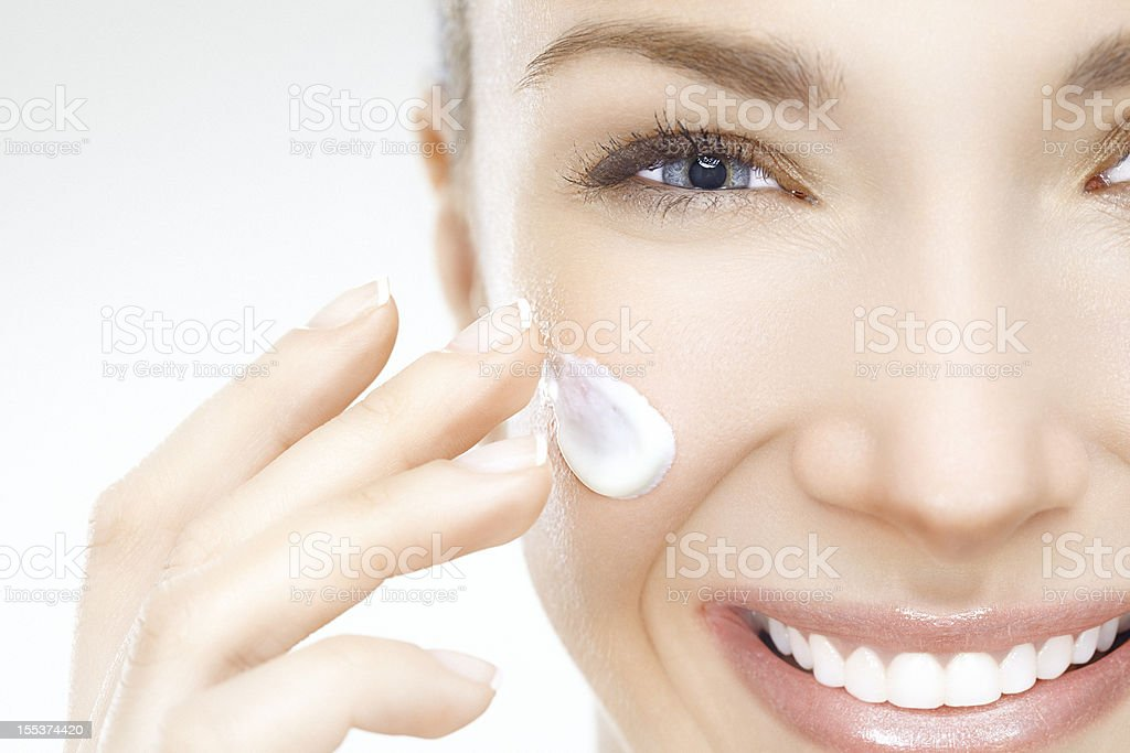 Close-up of a beautiful woman applying cream on her face stock photo