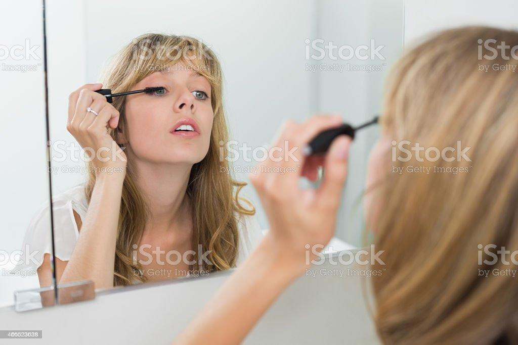 Close-up of a beautiful woman applying mascara stock photo